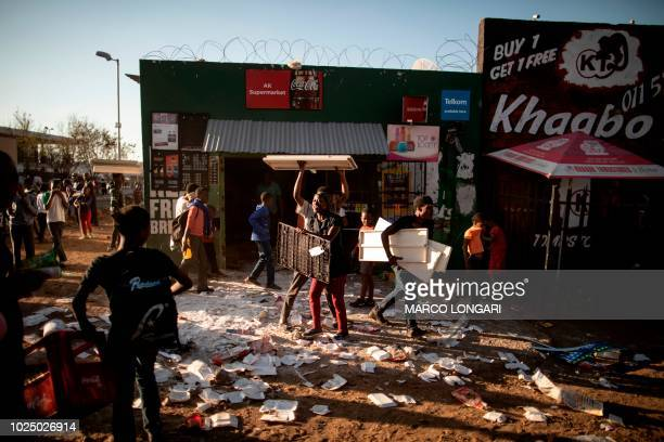 Looters take items from a foreignowned shop in Soweto Johannesburg on August 29 2018 during unrest that erupted after a foreign shop owner allegedly...