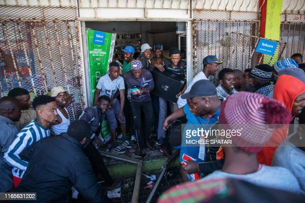 Looters take items from an alleged foreignowned shops during a riot in the Johannesburg suburb of Turffontein on September 2 2019 as angry protesters...