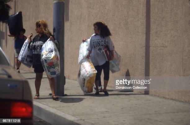 Looters walk away with goods during widespread riots that erupted after the acquittal of 4 LAPD officers in the videotaped arrest and beating of...