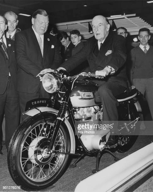 Lord Brabazon of Tara astride a Triumph Trophy motorcycle after opening the International Cycle and Motor Cycle Show at Earl's Court in London 10th...