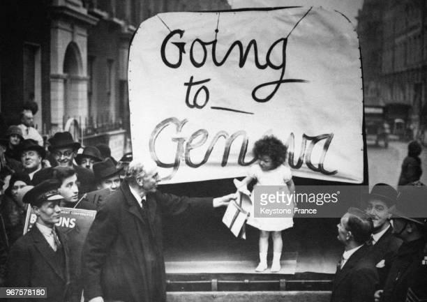 Lord Cecil délégué britannique à la SDN remet à la petite fille vêtue de blanc la pétition signée par près de 3 millions d'Anglais en faveur du...