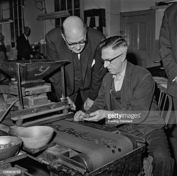 Lord Fiske , Chairman of the Decimal Currency Board, watches EG Davies on the production line for the new decimal coinage at the Royal Mint, UK, 16th...