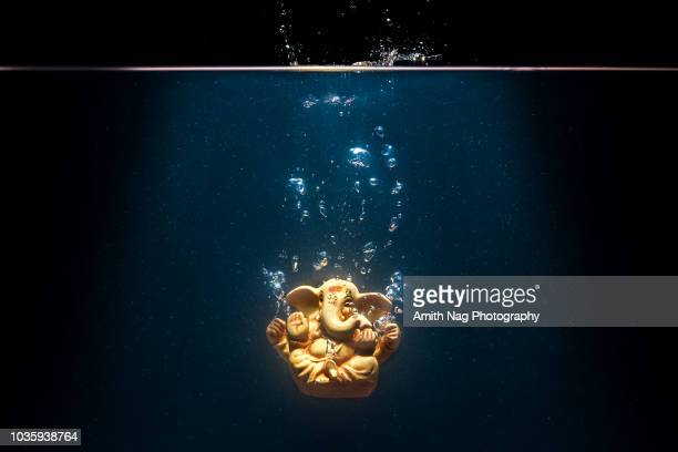 lord ganesha during immersion in a water body - ganesha stock photos and pictures
