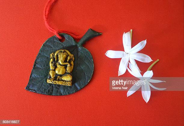 lord ganesha figurine-flowers-ethnic decor - hindu god stock photos and pictures