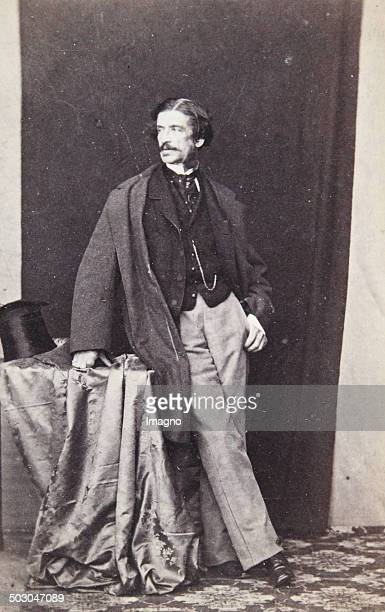 Lord in half profile in a dark frock coat dark skirt and bright pants cylinder on an Atelier table Full figure About 1865 Anonymous photograph