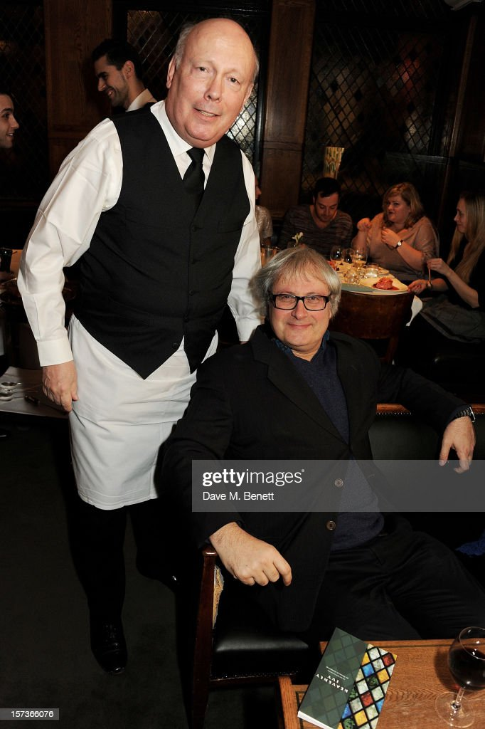 Lord Julian Fellowes (L), working as a waiter, and Simon Curtis attend One Night Only at The Ivy, featuring 30 stage and screen actors working as staff during dinner at The Ivy, in aid of The Combined Theatrical Charities, on December 2, 2012 in London, England.