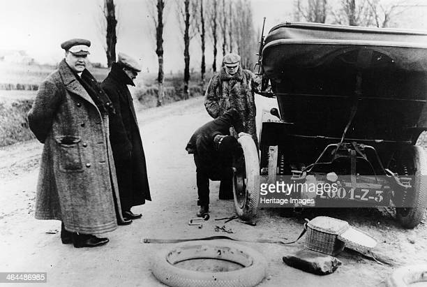 Lord Northcliffe's chauffeur changing a tyre Lord Northcliffe stands by the front of the vehicle watching his chauffeur at work Newspaper proprietor...
