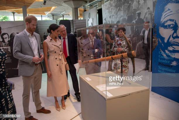 Lord Peter Hain Chair of The Nelson Mandela Centenary Committee shows Prince Harry Duke of Sussex and Meghan Duchess of Sussex a pickaxe similar to...
