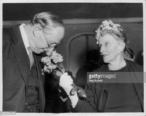 Lord Salisbury smelling a spray of roses held by Lady Nancy Astor at a charity luncheon at the Savoy Hotel London May 22nd 1959