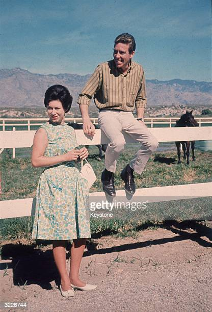 Lord Snowdon sitting on the fence next to Princess Margaret during a visit to a ranch in Arizona