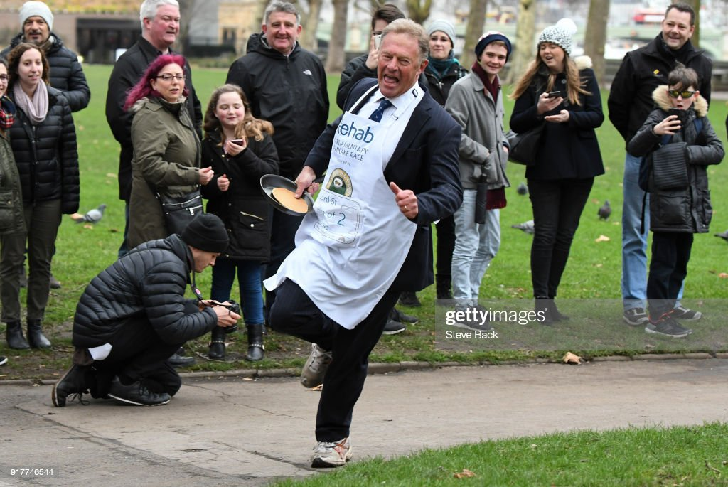 Lord St John of Bletso approaches the second corner in the annual Parliamentary Pancake Race in Victoria Tower Gardens on Shrove Tuesday on February 13, 2018 in London, England. The annual Pancake Race, which raises money for the charity Rehab, sees teams of politicians and journalists racing around a circuit whilst tossing pancakes in frying pans. The team of journalists won this year's event.
