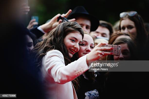 Lorde takes photos with her fans as she arrives at the 2014 New Zealand Music Awards at Vector Arena on November 20 2014 in Auckland New Zealand