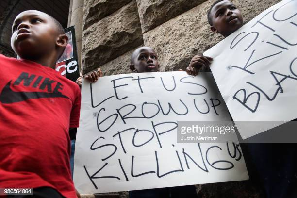 Lorde Watkins and his brothers Legend and Maceo join more than 200 people gathered for a rally to protest the fatal shooting of an unarmed black teen...