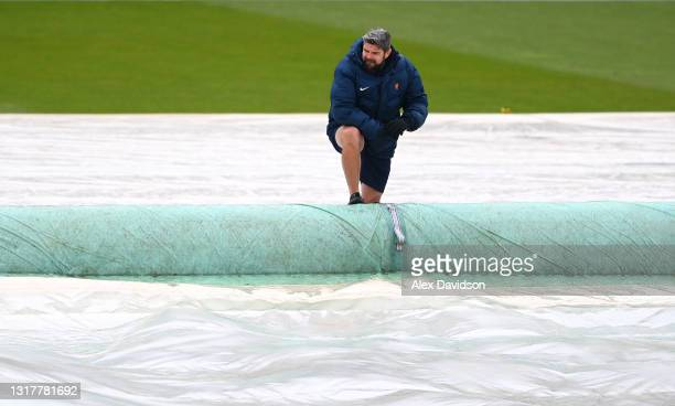 Lord's Head Groundsman Karl McDermott takes the covers off as play is delayed due to rain on Day One of the LV= Insurance County Championship match...