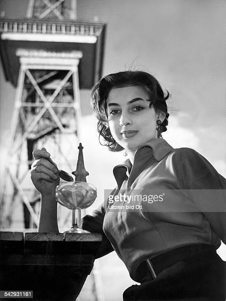 Lore Müller, eine 19jährige Berlinerin italienischerHerkunft, isst Eis, im Hintergrund der Funkturm in Berlin.- 1955