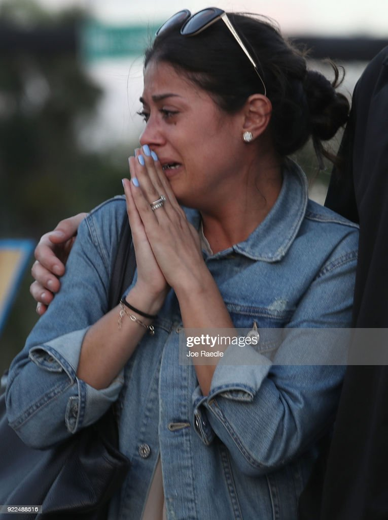 Loren Brovarnik cries as she visits a memorial setup in front of Marjory Stoneman Douglas High School in memory of the 17 people that were killed on February 14, on February 21, 2018 in Parkland, Florida. Police arrested 19-year-old former student Nikolas Cruz for killing 17 people at the high school.