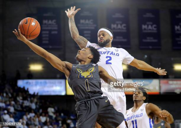 Loren Cristian Jackson of the Akron Zips takes a shot as Antwain Johnson of the Buffalo Bulls tries to block it during the second half at Alumni...