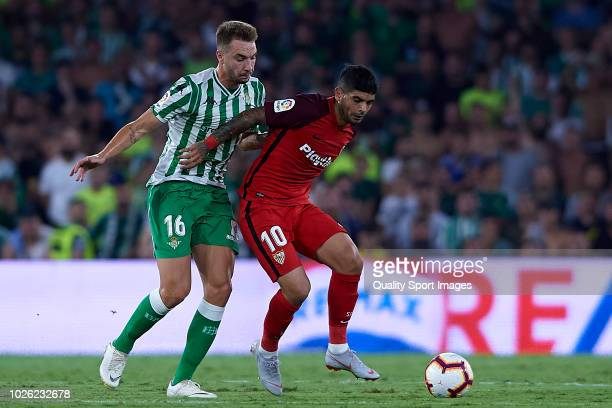 Loren Moron of Real Betis competes for the ball with Ever Banega of Sevilla FC during the La Liga match between Real Betis Balompie and Sevilla FC at...