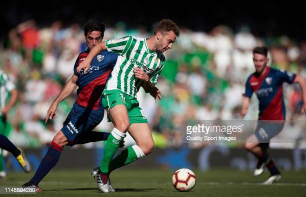 Loren of Real Betis competes for the ball with Etxeita of SD Huesca during the La Liga match between Real Betis Balompie and SD Huesca at Estadio...