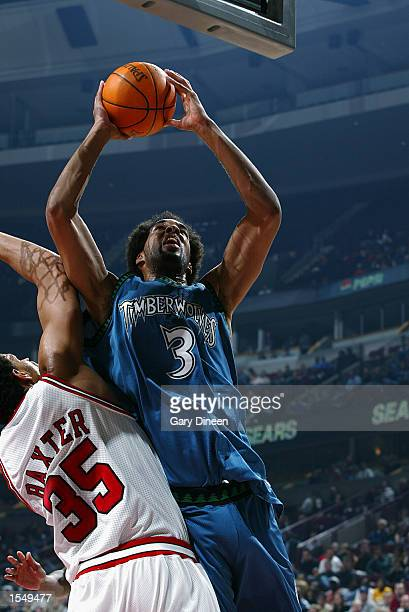 Loren Woods of the Minnesota Timberwolves goes to the basket against Lonny Baxter of the Chicago Bulls during the preseason game on October 21 2002...