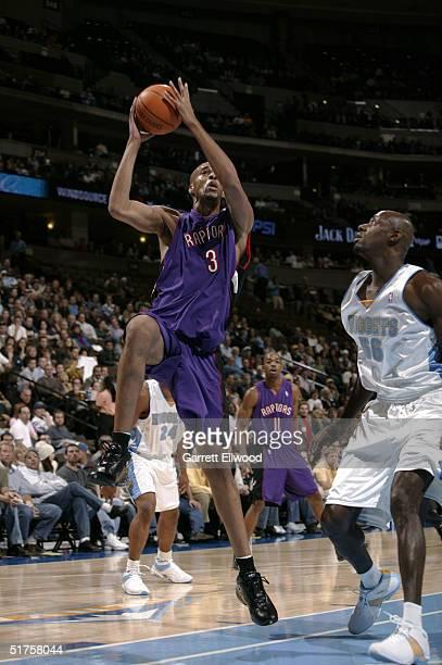 Loren Woods of the Toronto Raptors goes to the basket against Francisco Elson of the Denver Nuggets on November 17 2004 at Pepsi Center in Denver...