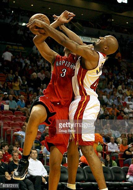 Loren Woods of the Toronto Raptors is fouled while going to the basket by Shandon Anderson of the Miami Heat at American Airlines Arena on April 11...