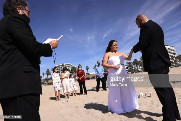 Lorena and Steven James are married by officiant Larry Morgia on the beach on Valentine's Day on February 14, 2021 in Huntington Beach, California....