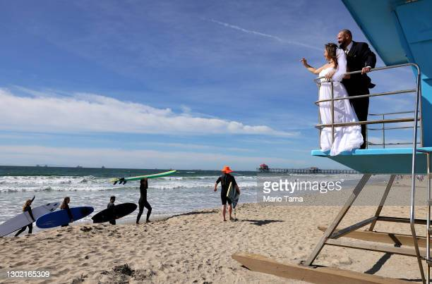 Lorena and Steven James wave to surfers while posing for photos on a lifeguard tower after they were married on the beach on Valentine's Day on...