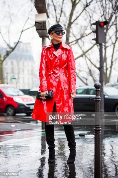 Lorena Campello wearing red laminated trench coat and Dior bag is seen in the streets of Paris before the Balmain show during Paris Fashion Week...