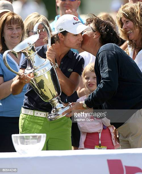 Lorena Ochoa of Mexico embraces Amy Alcott as she receives the trophy after the final round of the Kraft Nabisco Championship at Mission Hills...