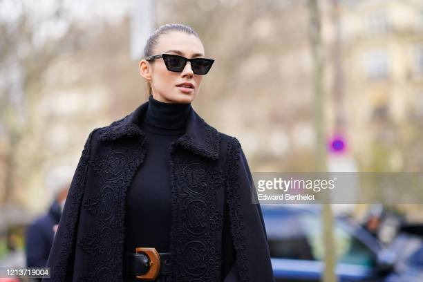 Lorena Rae wears sunglasses a black turtleneck pullover a belt a black lace mesh skirt a black long coat with embroidery outside Elie Saab during...
