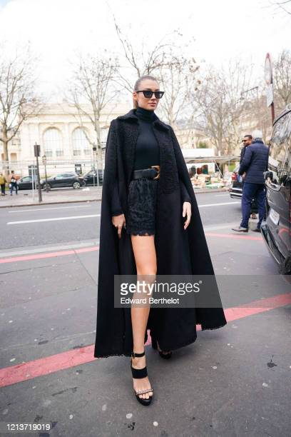 Lorena Rae wears sunglasses a black turtleneck pullover a belt a black lace mesh skirt a black long coat with embroidery shoes outside Elie Saab...