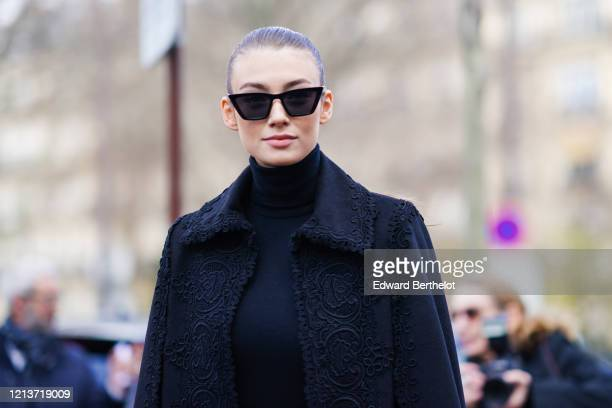 Lorena Rae wears sunglasses a black turtleneck pullover a black lace mesh skirt a black long coat with embroidery outside Elie Saab during Paris...
