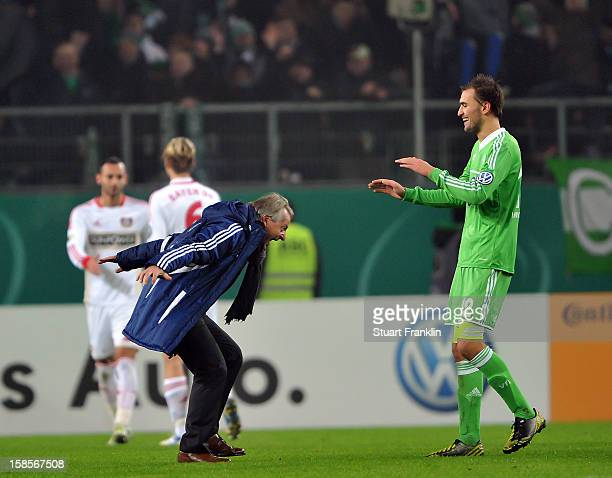 Lorenz Guenther Koestner head coach of Wolfsburg celebrates with winning goal scorer Bas Dost at the end of the round of 16 of the DFB cup match...