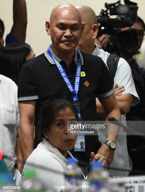 Lorenzana Delos Santos mother of 17yearold student Kian who was killed allegedly by police during an antidrug raid listen next to her husband Saldy...