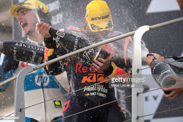 Lorenzo Balbassarri of Italy and Pons HP40 and Miguel Oliveira of Portugal and Red Bull KTM Ajo celebrate with champagne on the podium at the end of...