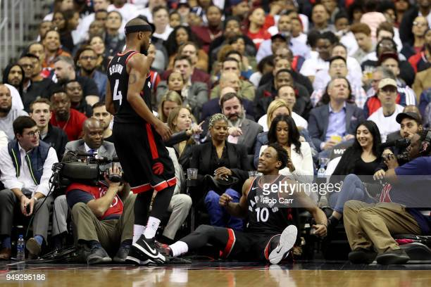Lorenzo Brown helps up DeMar DeRozan of the Toronto Raptors in the second half against the Washington Wizards during Game Three of Round One of the...