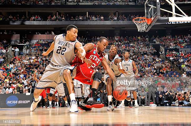 Lorenzo Brown of the North Carolina State Wolfpack goes for a lose ball against Otto Porter and Jason Clark of the Georgetown Hoyas in the first half...