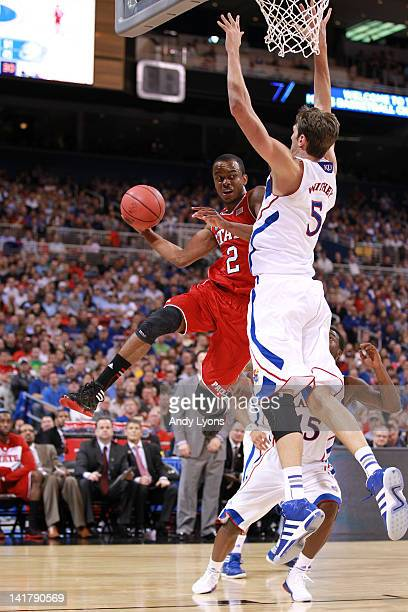 Lorenzo Brown of the North Carolina State Wolfpack looks to pass as he drives against Jeff Withey of the Kansas Jayhawks during the 2012 NCAA Men's...