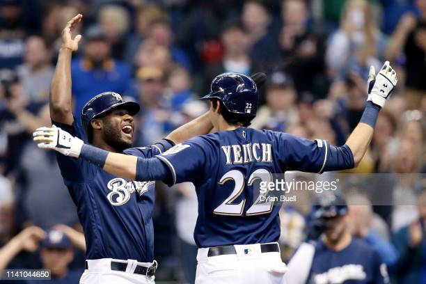 Lorenzo Cain and Christian Yelich of the Milwaukee Brewers celebrate after Yelich hit a home run in the first inning against the Chicago Cubs at...