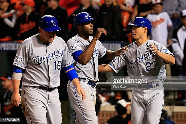 Lorenzo Cain Billy Butler and Norichika Aoki celebrate after scoring on Alex Gordon of the Kansas City Royals double to right field because of an...