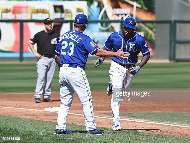 Lorenzo Cain of the Kansas City Royals celebrates with third base coach Mike Jirschele after hitting a third inning home run in a spring training...