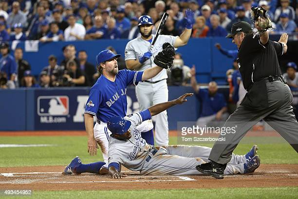 Lorenzo Cain of the Kansas City Royals scores a run in the first inning after RA Dickey of the Toronto Blue Jays attempts to make the tag during game...