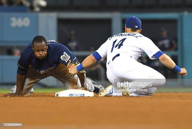 Lorenzo Cain of the Milwaukee Brewers beats the throw to Enrique Hernandez of the Los Angeles Dodgers as he takes second base on a wild pitch by...