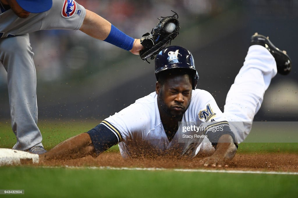 Lorenzo Cain #6 of the Milwaukee Brewers is tagged out at first base by Victor Caratini #7 of the Chicago Cubs during the first inning of a game at Miller Park on April 8, 2018 in Milwaukee, Wisconsin.