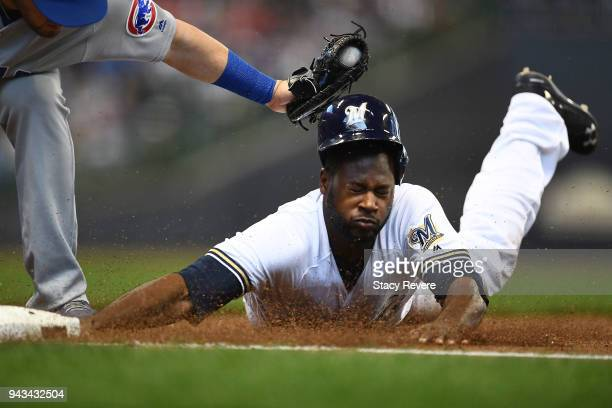 Lorenzo Cain of the Milwaukee Brewers is tagged out at first base by Victor Caratini of the Chicago Cubs during the first inning of a game at Miller...