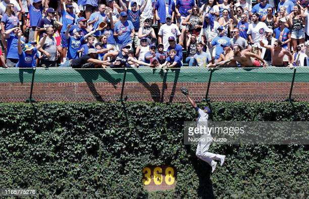 Lorenzo Cain of the Milwaukee Brewers is unable to catch the home run ball hit by Jason Heyward of the Chicago Cubs during the first inning of a game...