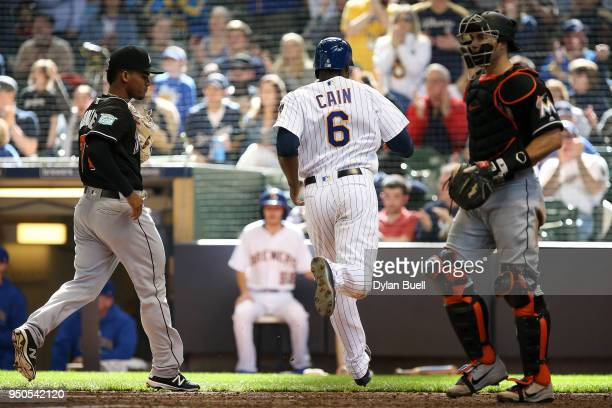 Lorenzo Cain of the Milwaukee Brewers scores a run past Merandy Gonzalez and JT Realmuto of the Miami Marlins in the eighth inning at Miller Park on...