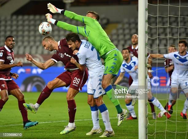 Lorenzo De Silvestri of Torino FC clashes with Daniele Dessena and Jesse Joronen of Brescia Calcio during the Serie A match between Torino FC and...