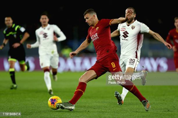 Lorenzo De Silvestri of Torino FC competes for the ball with Edin Dzeko of AS Roma during the Serie A match between AS Roma and Torino FC at Stadio...